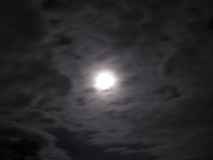The moon behind high thin clouds
