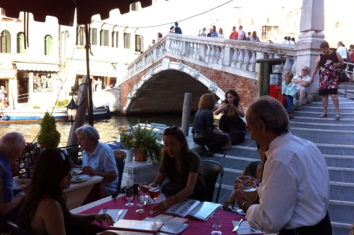 people having drinks and eating outside in the evening in Venice