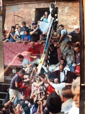 peopke sit on roofs and stand on balconies to see the Palio in Siena
