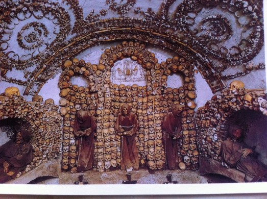 A picture of a postcard from the Capuchin Crypt which contains the bones of 4000 monks.