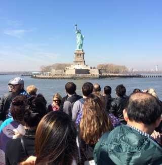 people on ship looking at Statue of Liberty