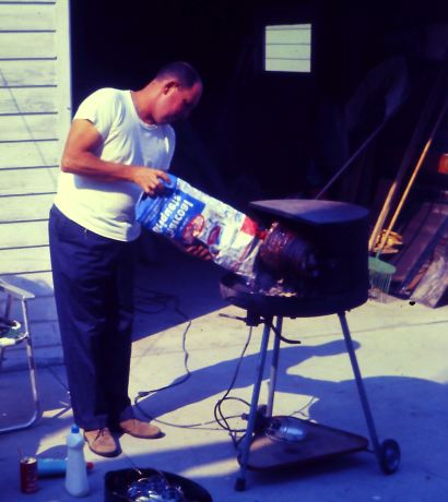 dad roasting a miami roll - add more charcoal