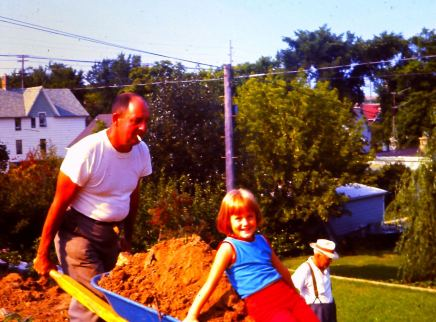 Dad hauling dirt with little sister riding in wheel barrow